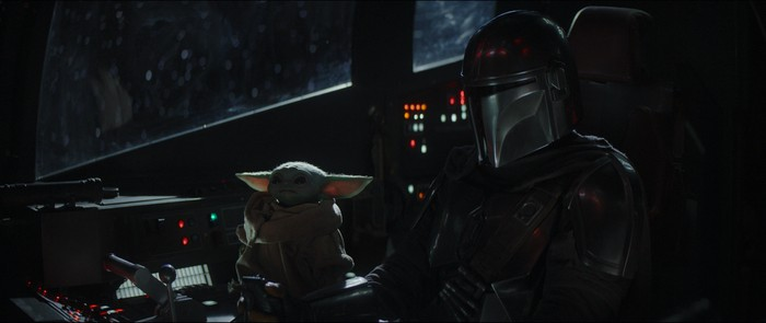 The Baby Yoda character and the Mandalorian sitting in the cockpit of a spaceship
