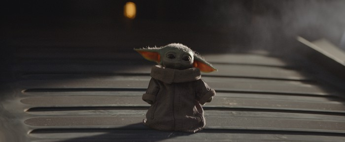 A small green creature with big ears wearing a robe, walking down a ramp