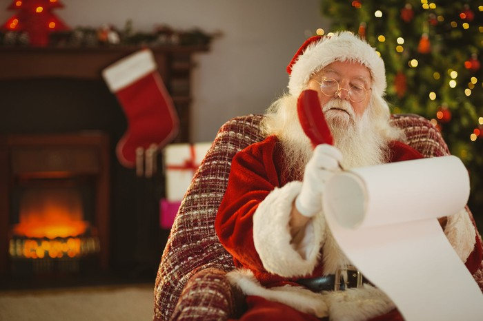 Santa Claus writing out his nice list, with a fireplace in the background.