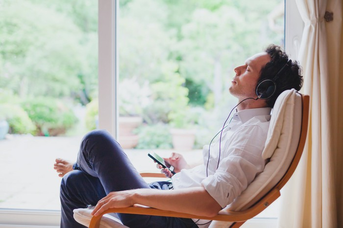 A man sitting in a chair with his eyes closed listening to music on headphones from his phone.