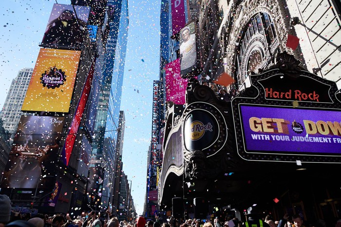 Confetti falls in New York City with Planet Fitness logos visible.