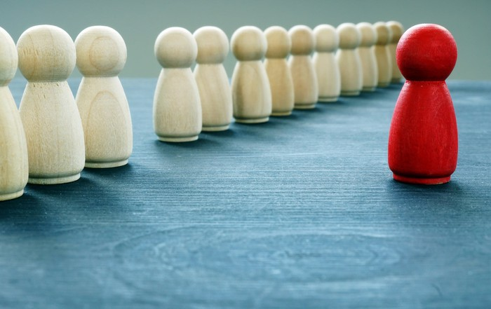 A red figurine stands out from line of cream colored figurines.