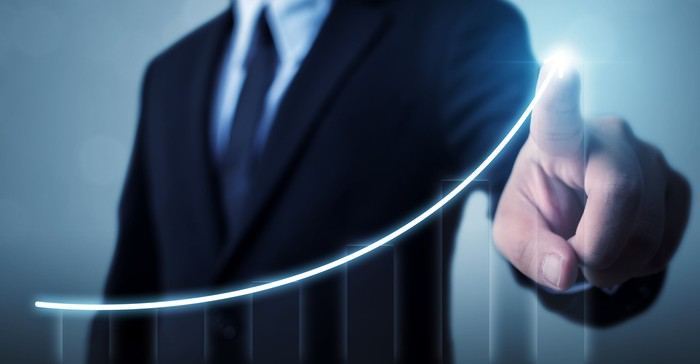 A person in a business suit pointing to an upwardly sloping line chart