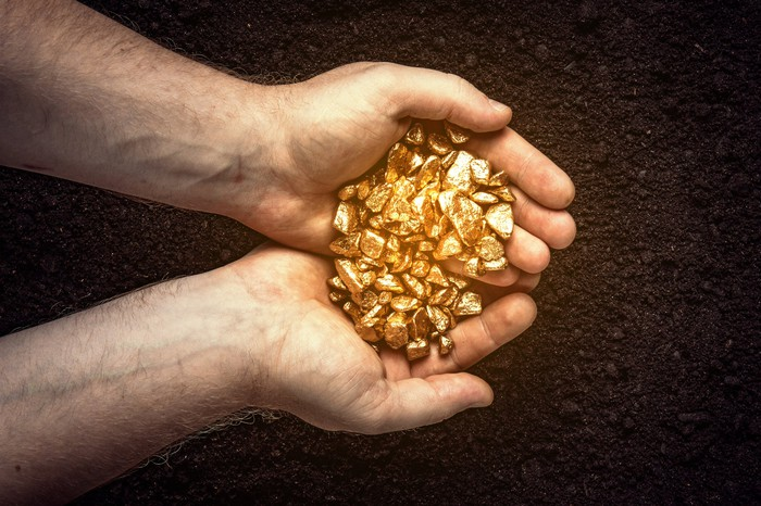 With cupped hands, a man holds gold nuggets.