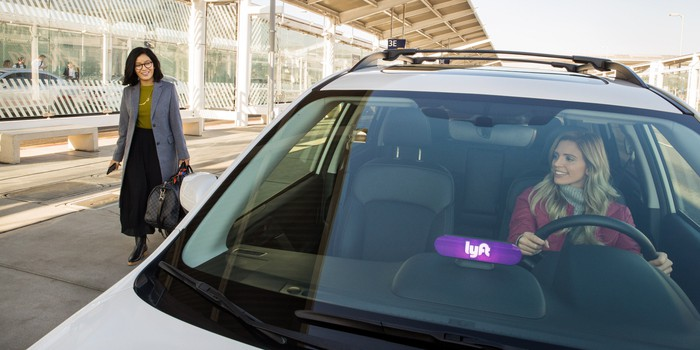 Woman walking up to a Lyft at an airport