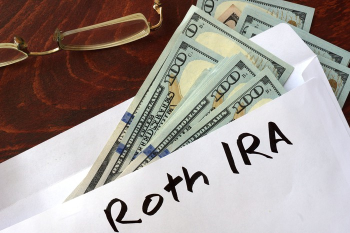 Envelope with hundred-dollar bills sticking out of it labeled Roth IRA on wooden surface next to eyeglasses