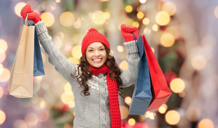 A woman in winter clothes holding up shopping bags and smiling