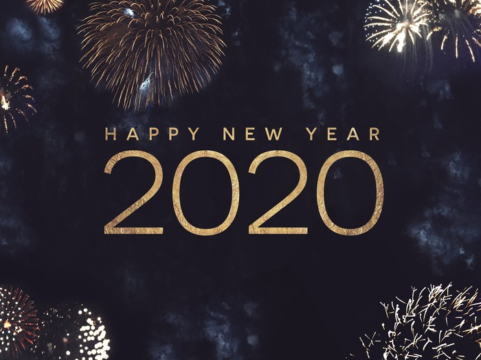 The words happy new year 2020 in gold against a dark blue background with fireworks