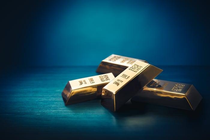 Gold bars shine amid a dark background.