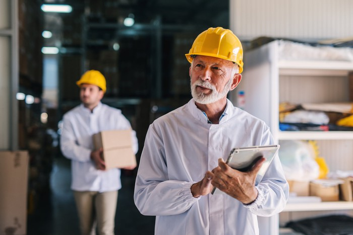 An older man in an industrial setting wears a yellow hard hat while cradling a tablet.