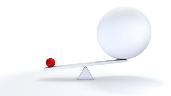 Graphic of small ball outweighing large ball on balance scale.