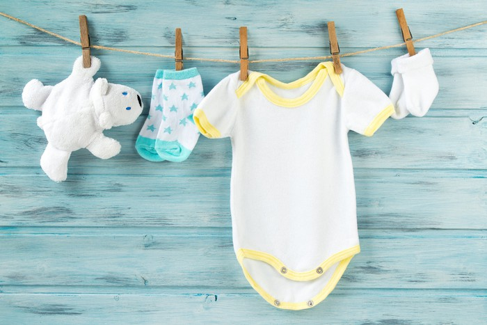 A baby's bodysuit, socks, and stuffed bear hang on a clothes line.