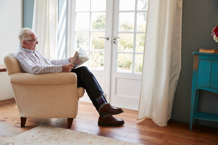 Older man reading newspaper in chair