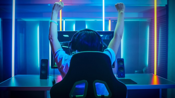 A young boy wearing a headset and celebrating with his fists in the air while playing a PC game.