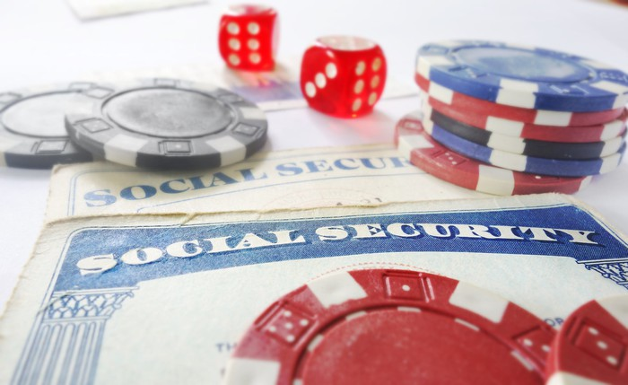 Red dice and casino chips lying atop two Social Security cards.