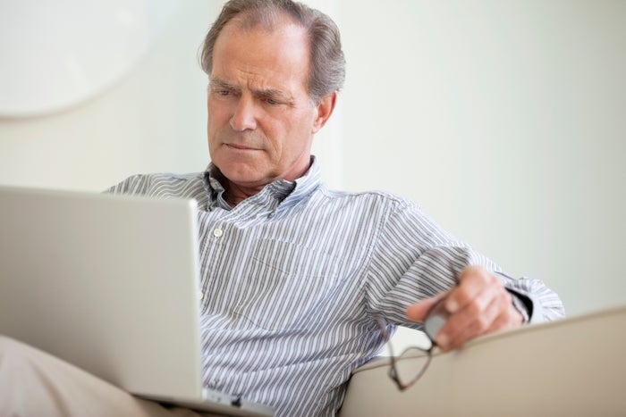 A senior man holding his glasses while seated on a couch and closely reading material on his laptop.