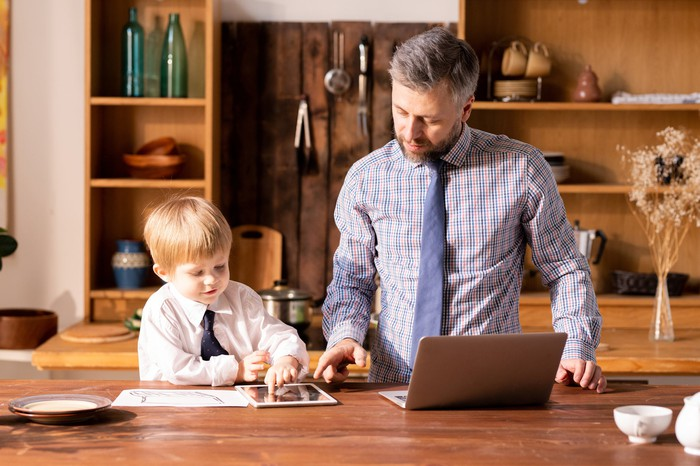 A man and a boy wearing ties look at a laptop, a tablet, and a printout on a table