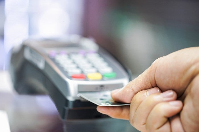 A hand placing a credit card into a chip-reading point-of-sale device.