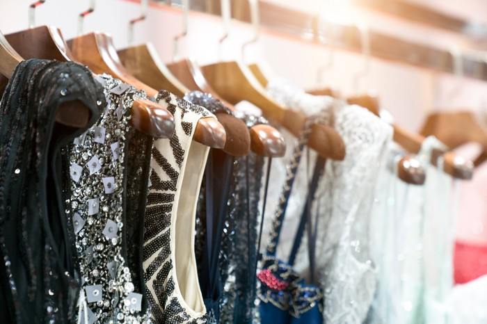 Sequined dresses, in black and white, on hangers in a store