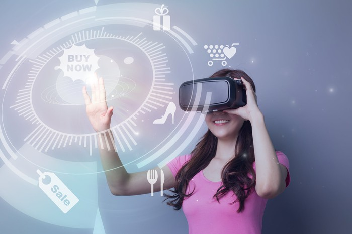 A woman wearing a VR headset and touching a Buy Now icon.