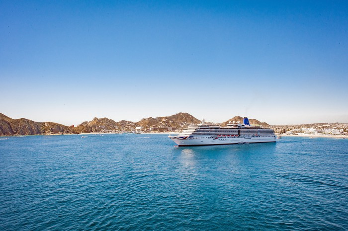 A cruise ship is anchored in the blue waters near Cabo San Lucas, Mexico.