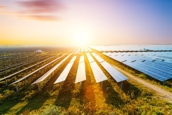 A field of solar panels with a bright sun setting in the background