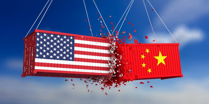Two freight containers, hoisted by unseen cranes, colliding mid-air. One is painted in the American flag and the other displays the Chinese flag.