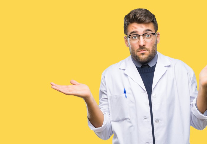 Doctor in lab coat with a confused facial expression and his hands in the air.