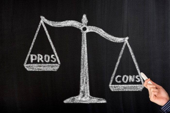 A chalk picture of pros being weighed against cons on a scale