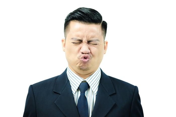 Businessman making a sour face.