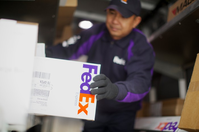 A FedEx delivery person grabs a package off a shelve in preparation for delivery