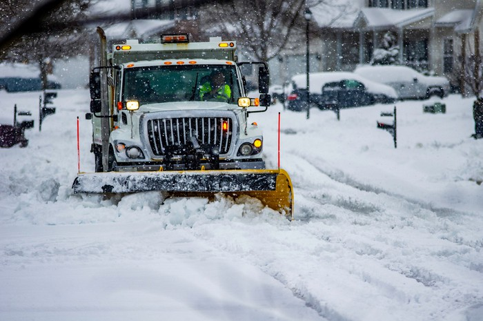 A work truck with yellow snow plow attachment clears a residential street after a winter storm.
