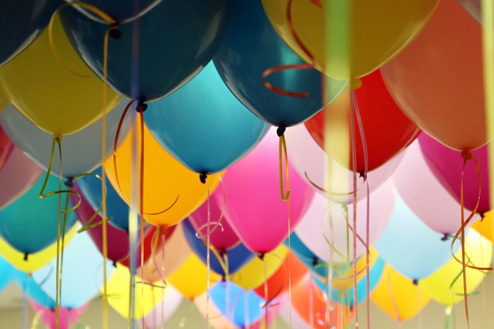 Helium-filled balloons in pink, yellow, and blue float together in a room.