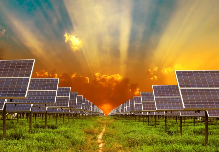 Rows of solar panels with the sun setting low on the horizon behind them