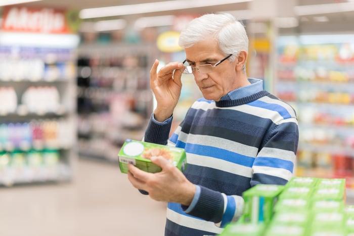 Older man adjusting eyeglasses while holding item in supermarket.