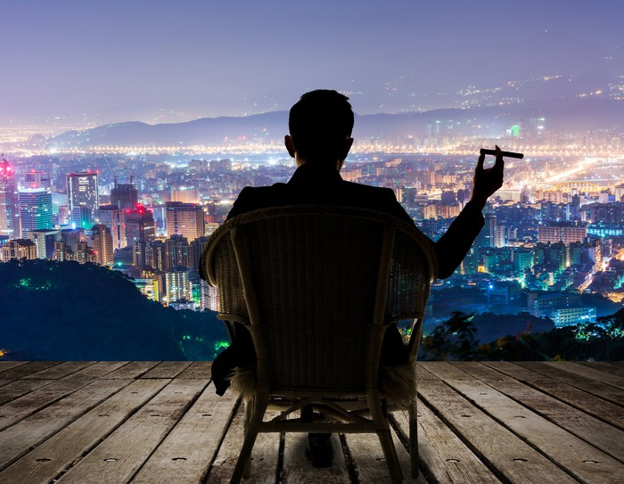 A man smokes a cigar in his deck chair from a high vantage point overlooking a city at night.