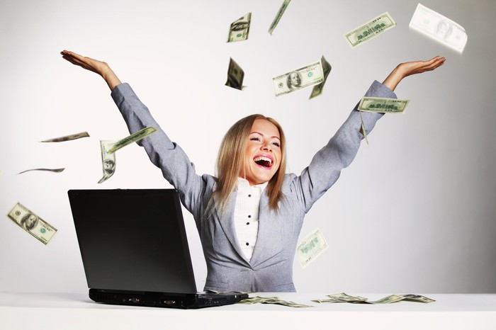 A young professionally dressed woman at her laptop, throwing hundred-dollar bills in the air with a huge smile.