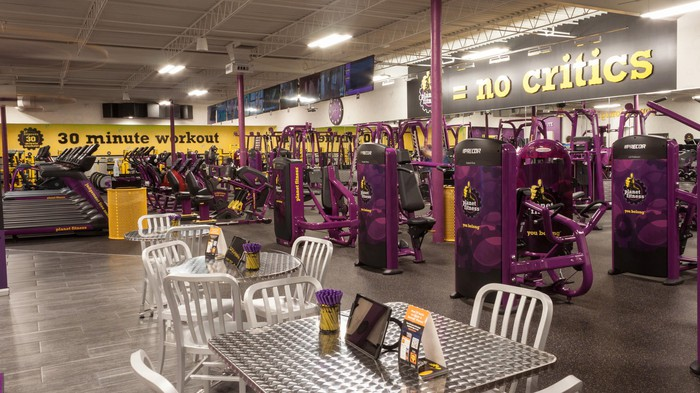 The inside of a Planet Fitness location with exercise machines and a seating area