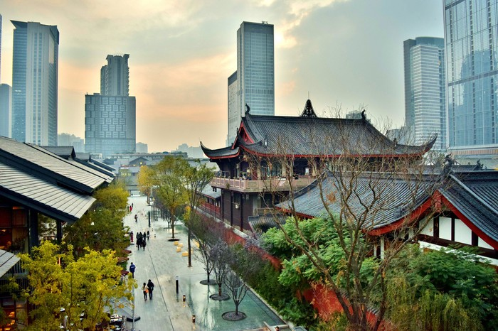 Traditional Chinese temples are pictured against a modern Chinese financial district.