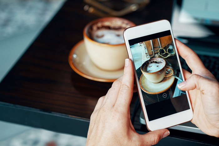 A person takes a picture of coffee with a smartphone.