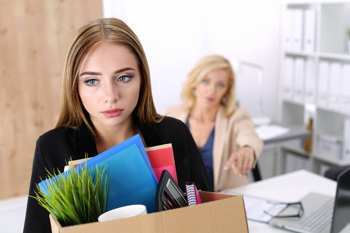 A professionally dressed woman sadly holds a box of belongings as another woman at a desk points at her to leave.