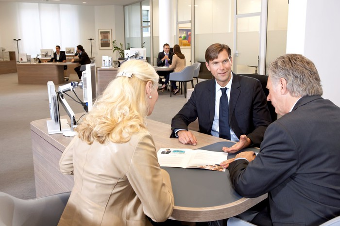 A couple consulting with a banker inside a bank branch.