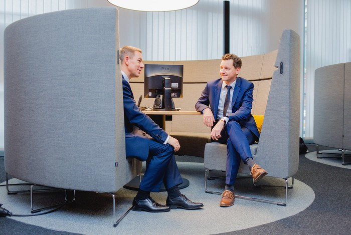 Two businessmen having a discussion inside a bank branch.