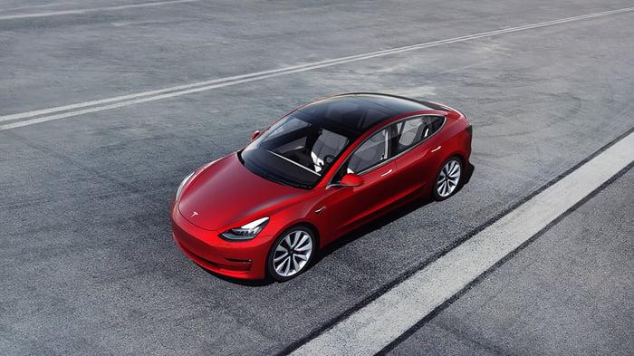 A Tesla Model 3 parked on a wide road.