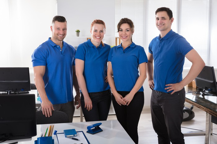 Four janitors in blue uniforms pose in an office space.