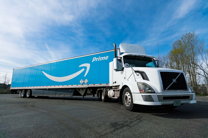 Amazon delivery trailer with blue and white arrow logo parked in a lot.