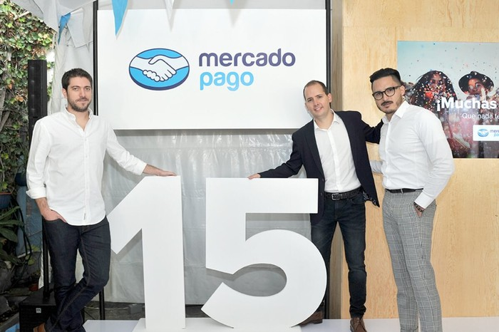Three people in front of a Mercado Pago banner and the number 15.