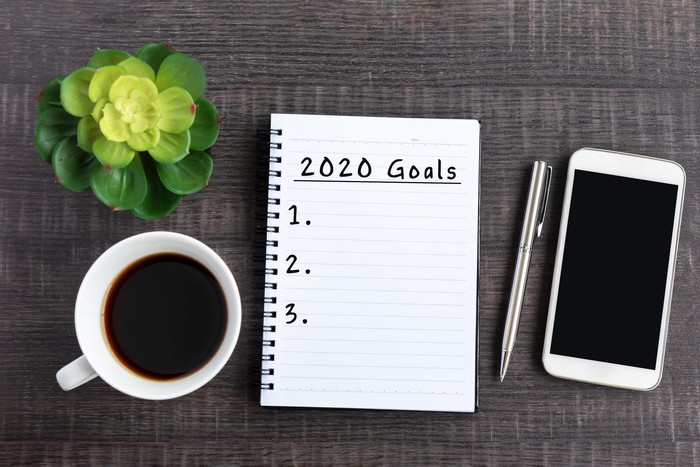 "A notebook open to a page reading ""2020 goals"" and a numerical list from one to three"