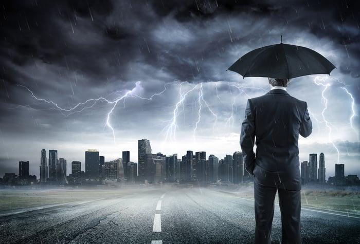 A businessman standing under an umbrella watching a lightning storm over a city.