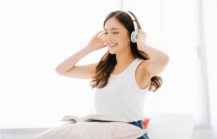 A smiling young woman listens to music through headphones.